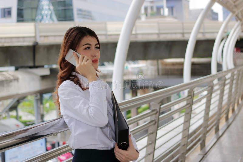 Jeune femme d'affaires asiatique parlant au téléphone et tenant le dossier de document dans des ses mains au fond urbain de ville image stock