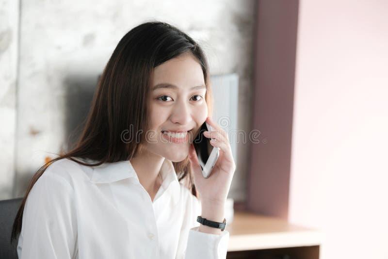 Jeune femme d'affaires asiatique parlant le téléphone intelligent souriant avec heureux photos stock