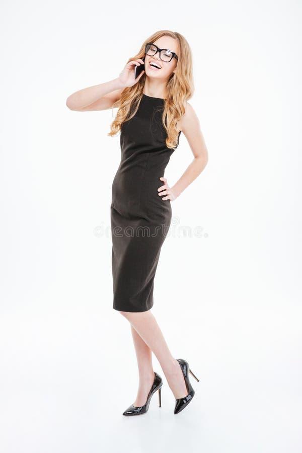 Jeune femme d'affaires attirante heureuse parlant sur le téléphone portable et rire image stock