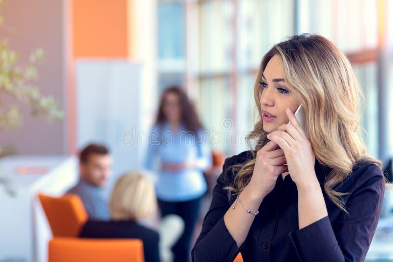 Jeune femme d'affaires attirante parlant au téléphone portable dans le bureau, ses collègues sur le fond images stock