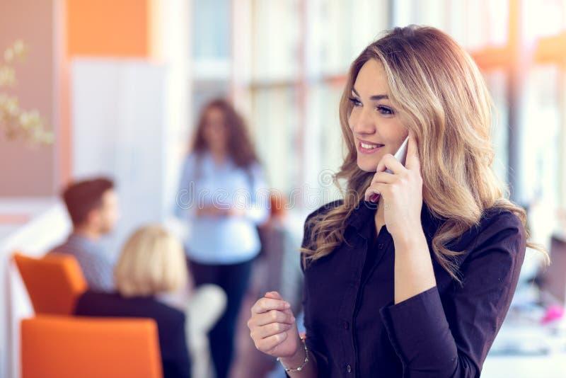 Jeune femme d'affaires attirante parlant au téléphone portable dans le bureau, ses collègues sur le fond photographie stock