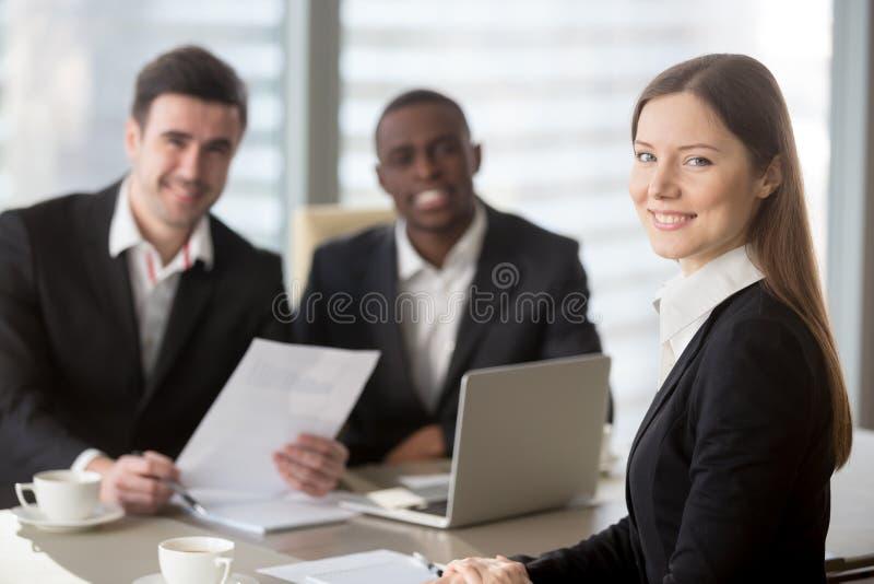 Jeune femme d'affaires attirante regardant l'appareil-photo, équipe femelle le photo libre de droits