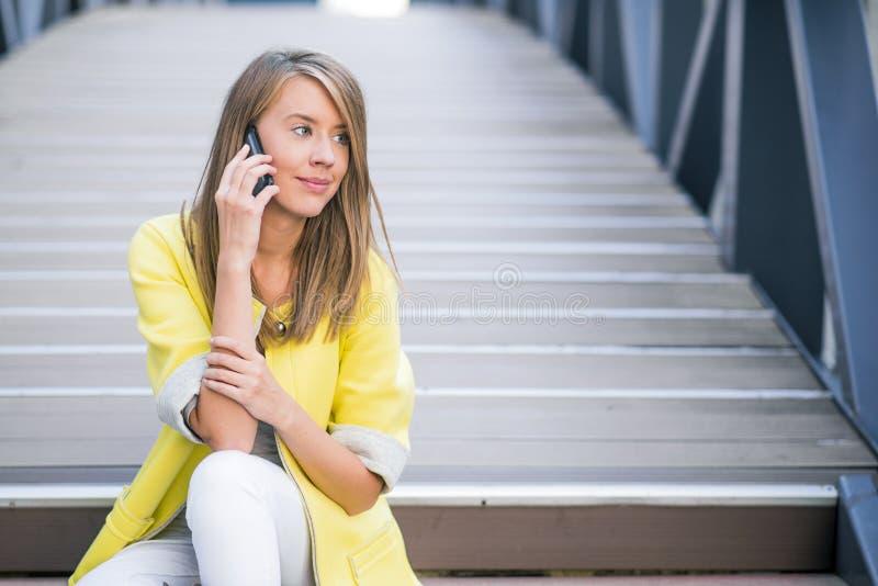 Jeune femme d'affaires attirante s'asseyant sur le pont et à l'aide du téléphone intelligent image stock