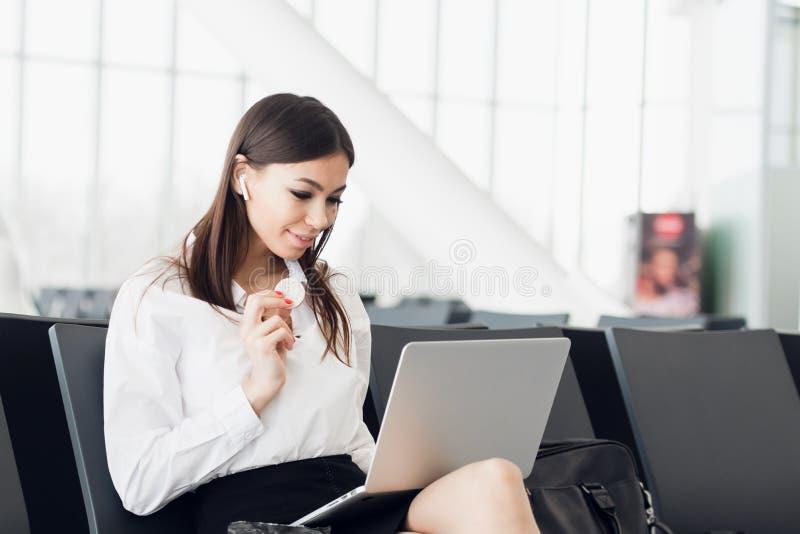 Jeune femme d'affaires avec l'ordinateur portable et le casse-croûte sain dans sa main se reposant à la porte terminale de départ photos stock