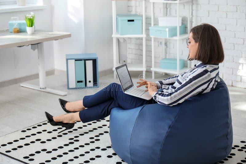 Jeune femme d'affaires avec l'ordinateur portable se reposant sur la chaise de sac à haricots dans le bureau photos stock