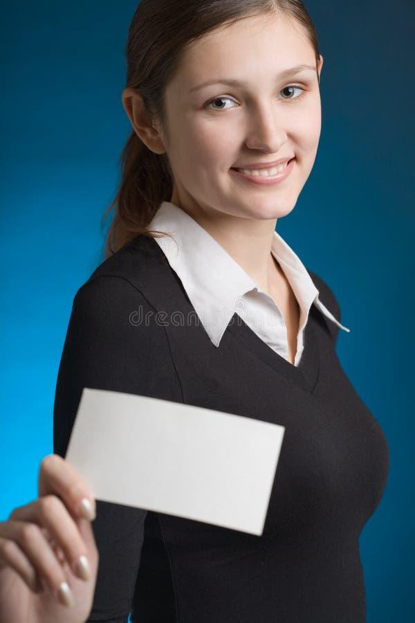 Jeune femme d'affaires avec la carte vierge d'affaires ou de note sur le CCB bleu photographie stock