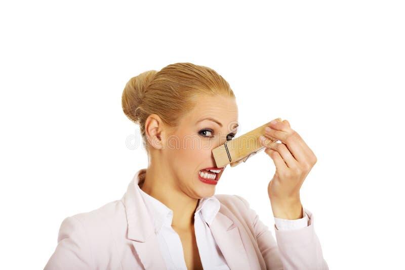 Jeune femme d'affaires avec la pince à linge énorme sur son nez Empeste le concept photographie stock