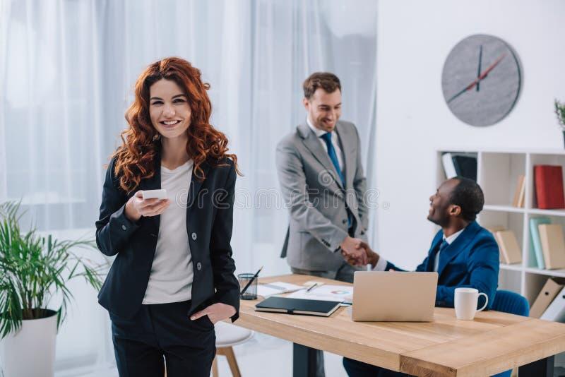 Jeune femme d'affaires avec la secousse de smartphone et de deux hommes d'affaires photos stock