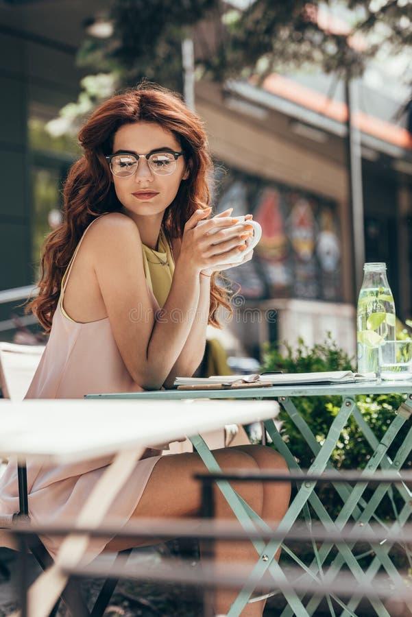 jeune femme d'affaires avec la tasse de café se reposant à la table avec le carnet photographie stock libre de droits