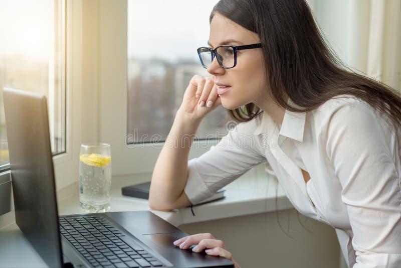 Jeune femme d'affaires avec le fonctionnement en verre sur l'ordinateur portable à la maison, dans l'hôtel, parlant sur la vidéo, photo libre de droits