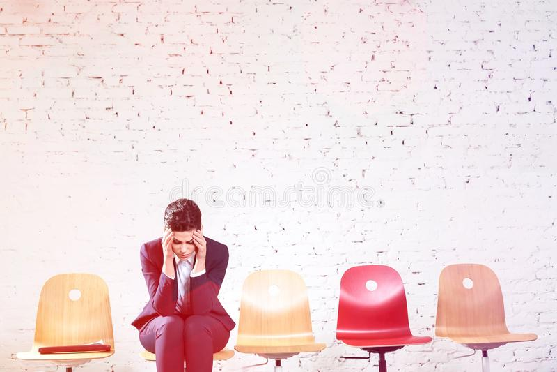 Jeune femme d'affaires avec le mal de t?te se reposant contre le mur de briques blanc au lobby de bureau photos stock