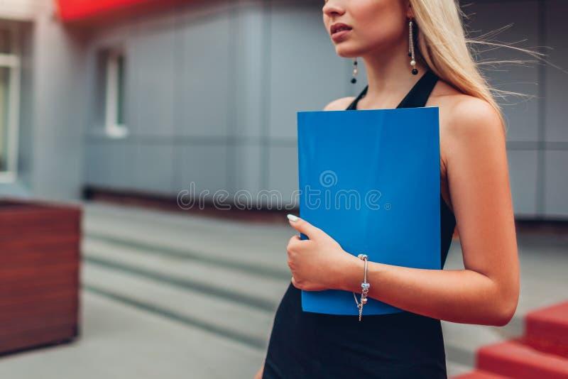 Jeune femme d'affaires blonde tenant se réunir de attente de dossier par le centre d'affaires dans la ville closeup photo libre de droits
