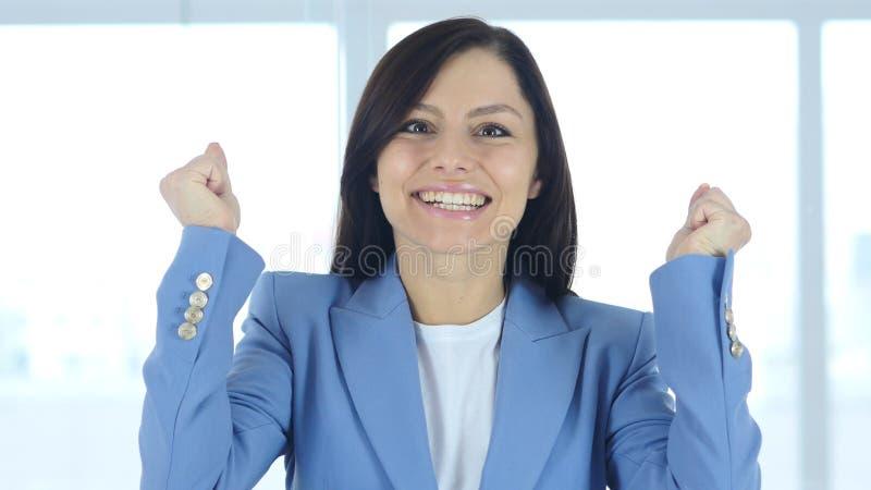 Jeune femme d'affaires célébrant le succès dans son bureau photographie stock libre de droits