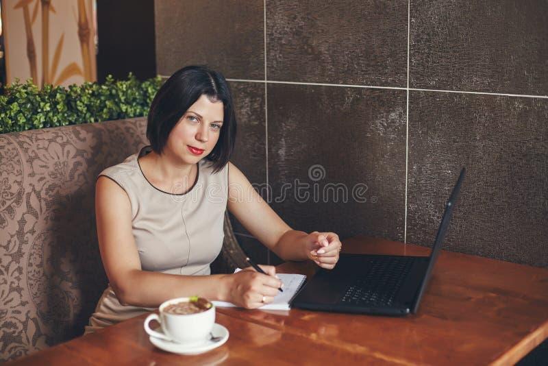 Jeune femme d'affaires caucasienne avec l'ordinateur portable et le carnet Femme en café photo stock
