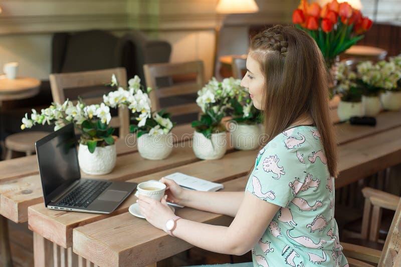 Jeune femme d'affaires caucasienne en café se reposant à la table avec le regard fixe réfléchi images stock