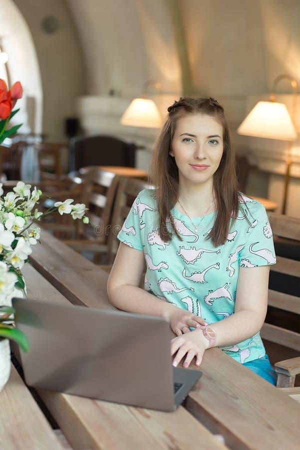 Jeune femme d'affaires caucasienne en café se reposant à la table avec le regard fixe réfléchi image libre de droits