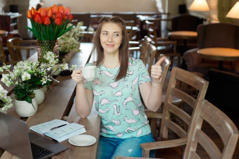 Jeune femme d'affaires caucasienne en café se reposant à la table avec le regard fixe réfléchi photos stock