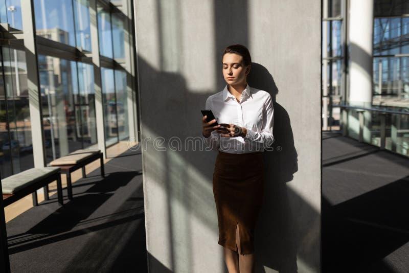 Jeune femme d'affaires caucasienne se penchant contre le mur et à l'aide du téléphone portable dans le bureau photos stock