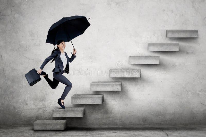 Jeune femme d'affaires courant sur l'escalier image stock
