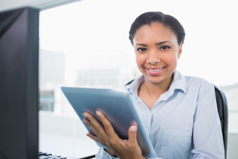 Jeune femme d'affaires d'une chevelure foncée joyeuse à l'aide d'un PC de comprimé photo libre de droits