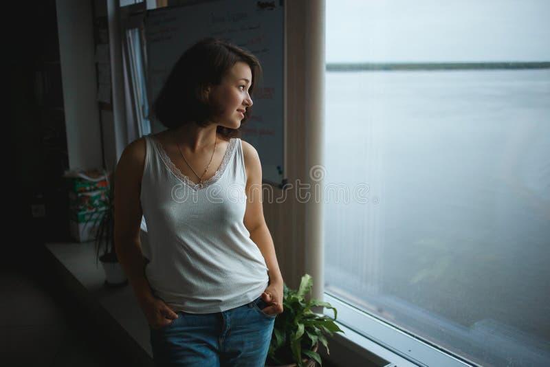 Jeune femme d'affaires dans des vêtements sport regardant à la fenêtre dans le bureau images stock