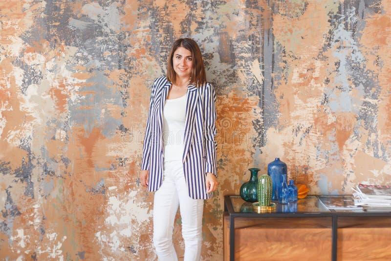 Jeune femme d'affaires dans la position rayée de veste au mur images libres de droits