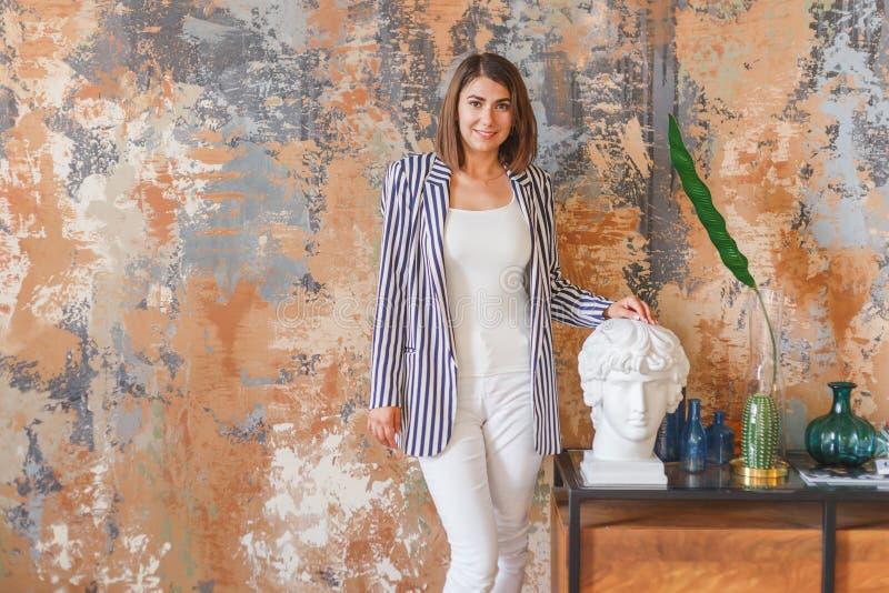 Jeune femme d'affaires dans la position rayée de veste près de l'objet d'art images libres de droits