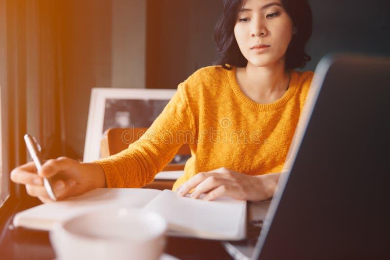 Jeune femme d'affaires dans la robe jaune se reposant à la table en café images stock