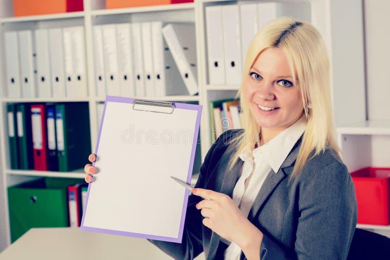 Jeune femme d'affaires dans le bureau se dirigeant au presse-papiers images libres de droits