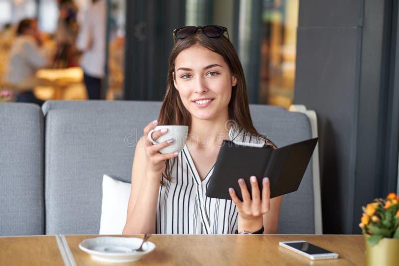 Jeune femme d'affaires dans un caf? lisant un ebook et buvant du caf? images libres de droits