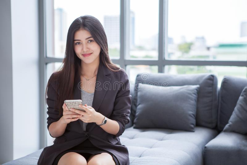 jeune femme d'affaires de bel Asiatique sûr souriant et à l'aide du smartphone situant sur le sofa, sur la fenêtre à l'arrière-pl photos libres de droits