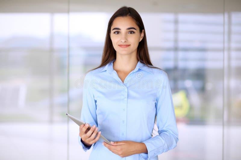 Jeune femme d'affaires de brune ou fille d'étudiant regardant l'appareil-photo photo stock