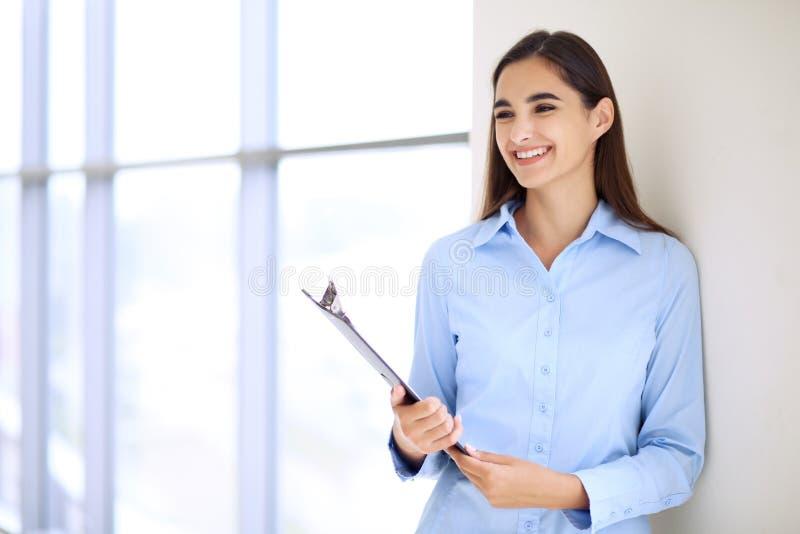 Jeune femme d'affaires de brune ou fille d'étudiant regardant l'appareil-photo image stock