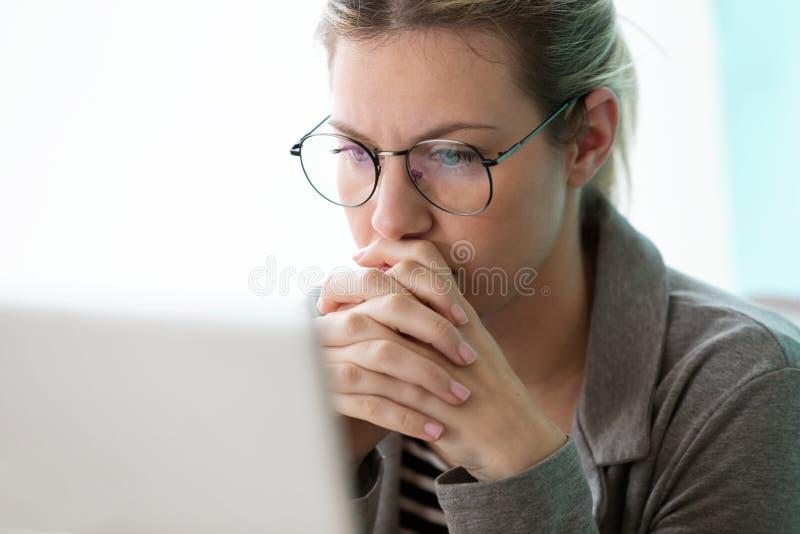 Jeune femme d'affaires de concentré regardant son ordinateur tout en pensant dans le bureau photo stock