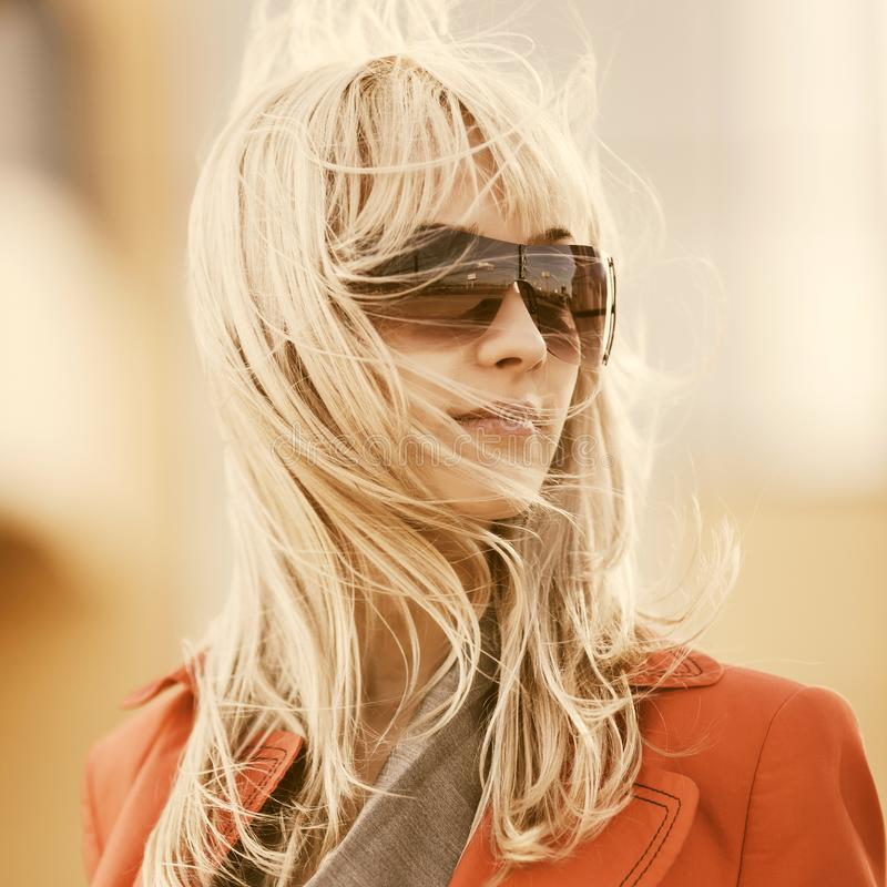 Jeune femme d'affaires de mode dans des lunettes de soleil marchant sur la rue de ville images libres de droits