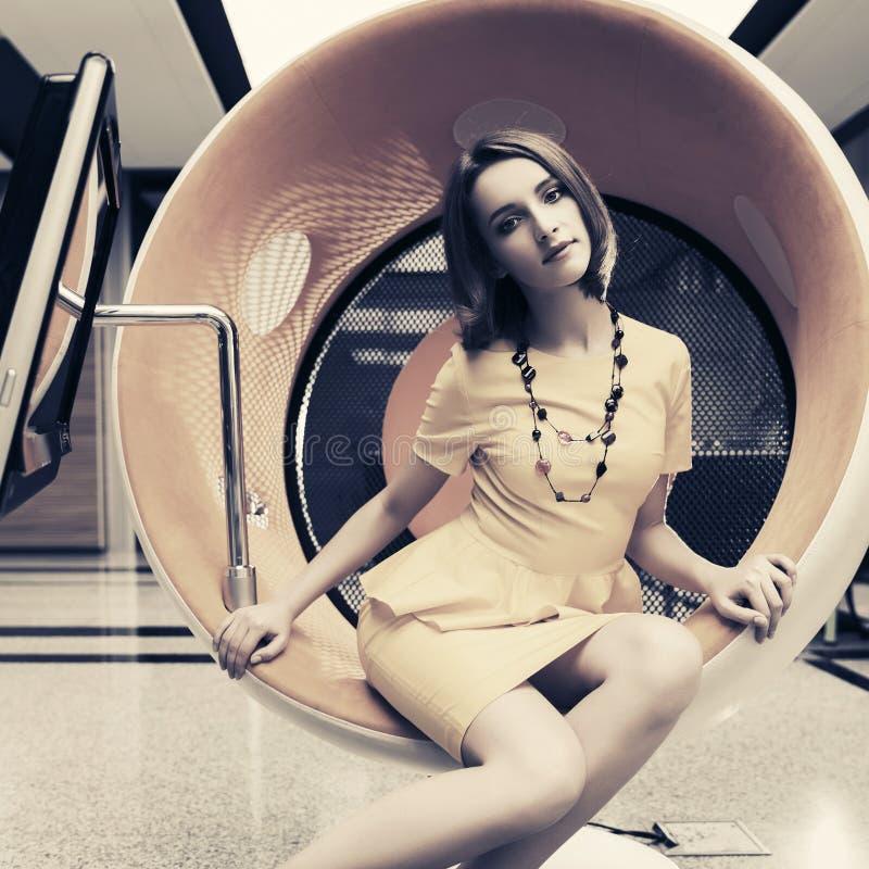 Jeune femme d'affaires de mode s'asseyant sur la chaise d'ordinateur dans le bureau photo libre de droits