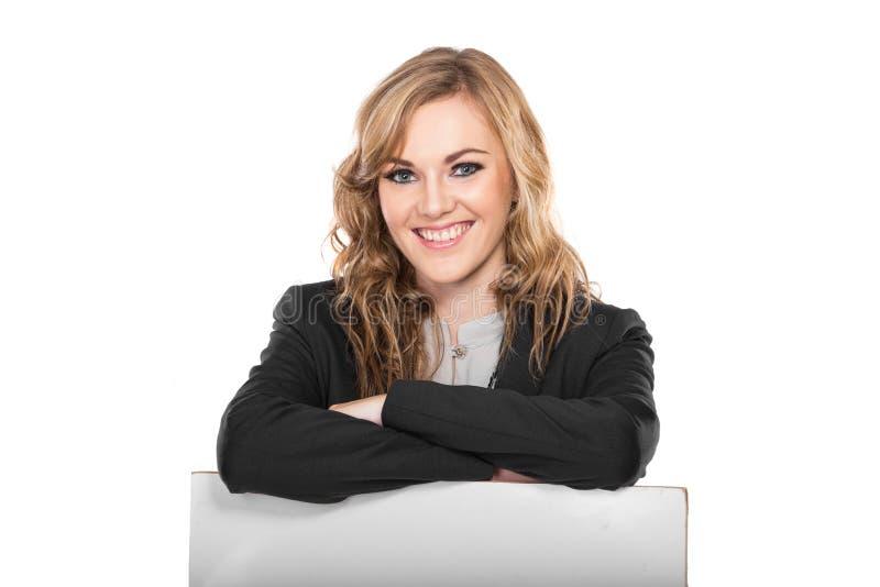 Jeune femme d'affaires de sourire jugeant le signe vide d'isolement sur le blanc image stock