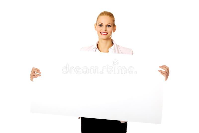 Jeune femme d'affaires de sourire tenant la bannière vide photos stock