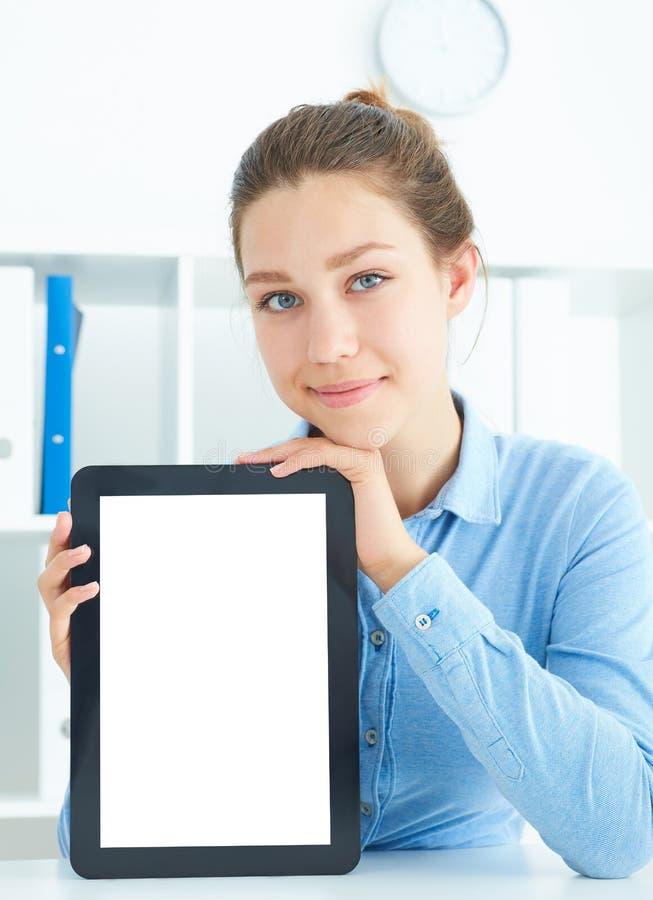 Jeune femme d'affaires de sourire tenant le comprimé dans des mains se reposant au bureau photos libres de droits