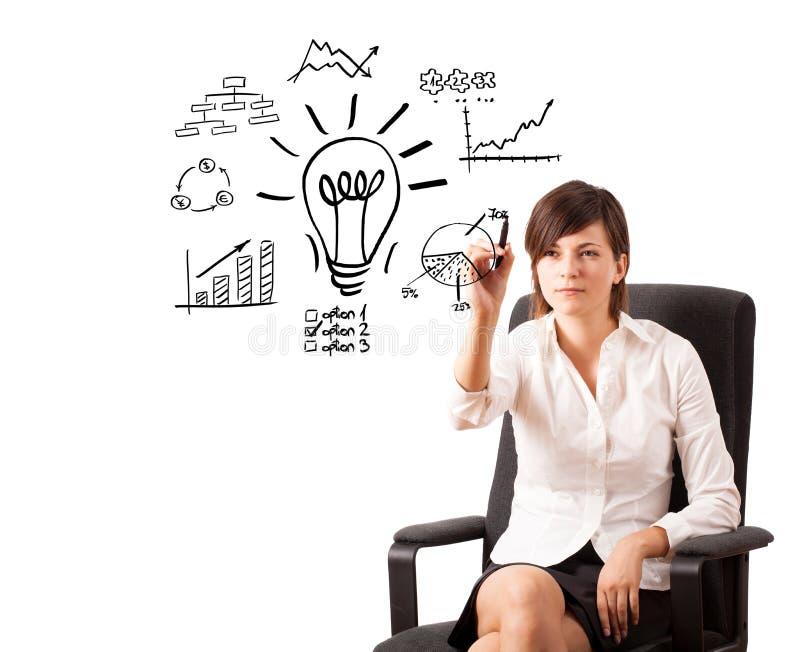 Jeune femme d'affaires dessinant l'ampoule avec de divers tableaux photographie stock libre de droits