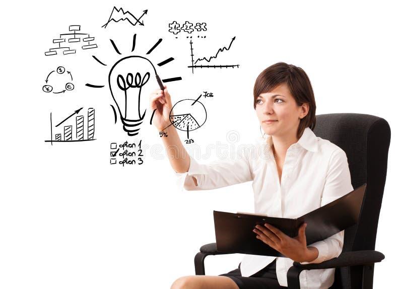 Jeune femme d'affaires dessinant l'ampoule avec de divers tableaux photo stock