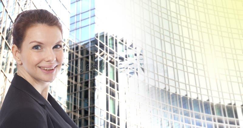 Jeune femme d'affaires devant le fond brouillé d'immeuble de bureaux photo stock
