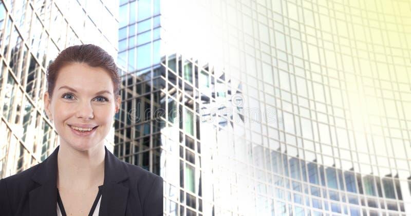 Jeune femme d'affaires devant le fond brouillé d'immeuble de bureaux photo libre de droits