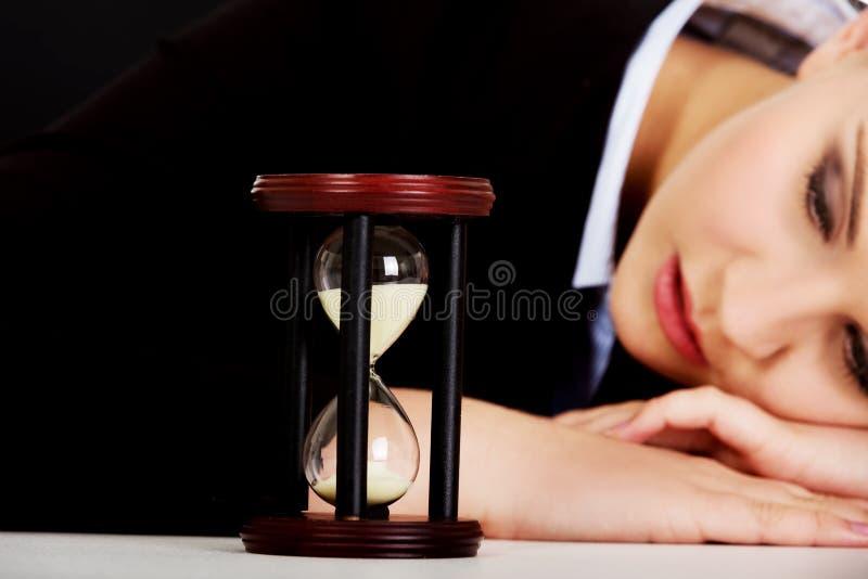 Jeune femme d'affaires dormant sur le bureau avec le sablier photo stock