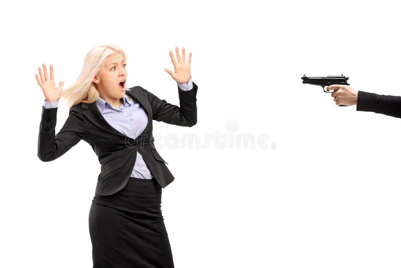 Jeune femme d'affaires effrayée d'une arme à feu photographie stock libre de droits