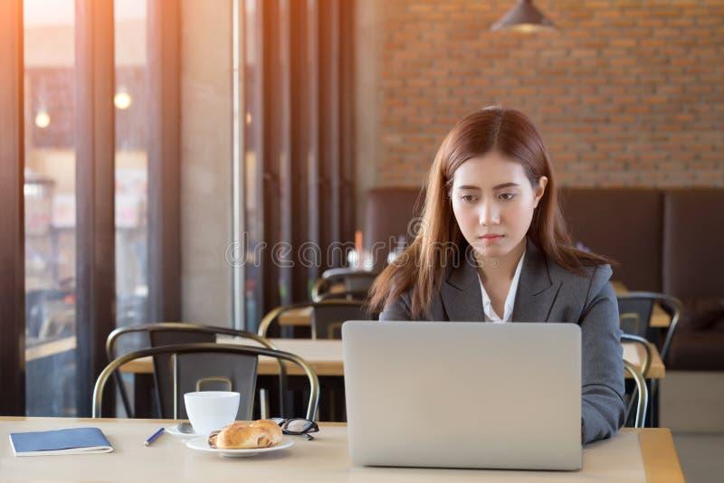 Jeune femme d'affaires ennuyée travaillant en café photo libre de droits