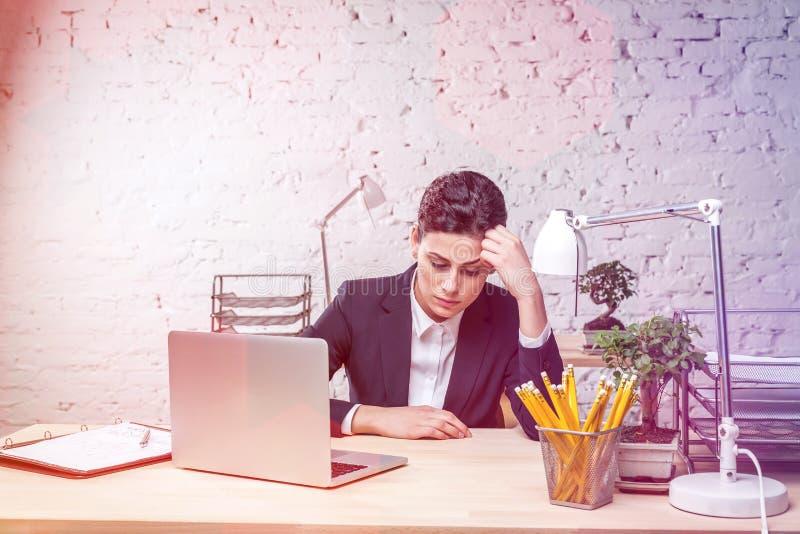 Jeune femme d'affaires ennuy?e s'asseyant avec l'ordinateur portable au bureau contre le mur de briques dans le bureau photos libres de droits