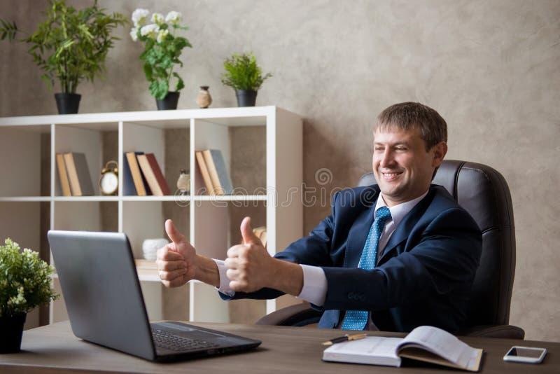 Jeune femme d'affaires enthousiaste heureuse s'asseyant sur le lieu de travail montrant la classe Négociations en ligne photographie stock libre de droits