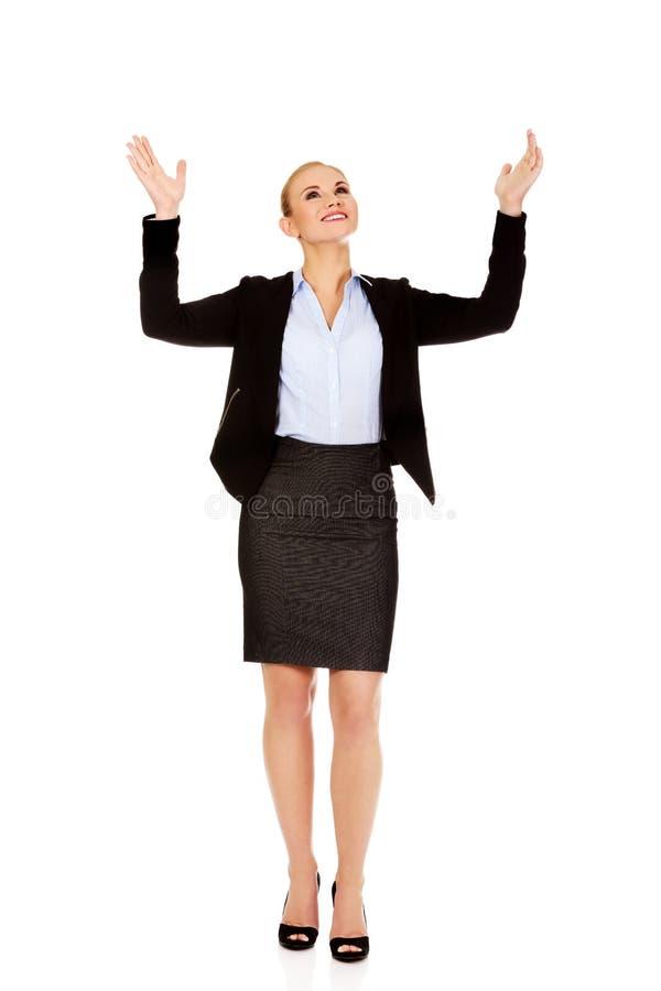 Jeune femme d'affaires essayant d'attraper quelque chose photo stock