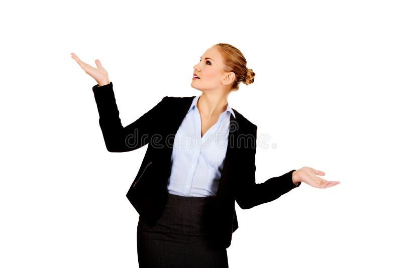 Jeune femme d'affaires essayant d'attraper quelque chose photographie stock